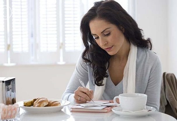 Hispanic woman writing letter in cafe